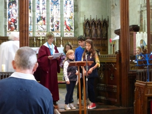 Children from Rocky's Plaice assist with prayers.