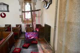 A large wooden cross draped in red ribbons