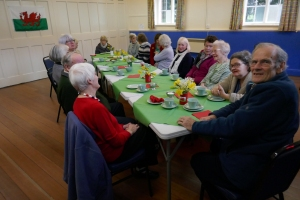 Enjoying the Bara Brith and Welsh Cakes at the St David's Day Guilsfield Gets Together Coffee Morning with daffodils on the table and a Welsh flag on the wall