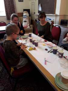Children painting and decorating rocks on the theme of Mothering Sunday ready for the Service the following day